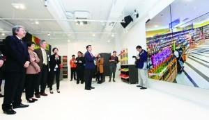 20150205 職訓局零售體驗廊 助學生模擬實習 職訓局啟用培訓模擬商店「零售體驗廊」,學生可透過LED大屏幕展示的互動虛擬實景,即時作互動學習。圖左一為財政司長曾俊華。(職訓局提供)