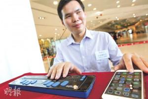 香港失明人協會何家樑平日會利用具藍牙功能的點字器,接駁手機後便能透過觸摸凸字來操作手機及打字。他即場以點字器上的藍色鍵打字,輕輕連按數下,不消數秒就在手機上打到「Good morning」等字句。(郭慶輝攝)