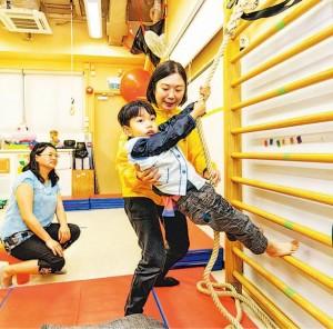 協康會物理治療師盧美玲(右後排),為有發展遲緩的承天(右前排)作拉繩訓練,動作可鍛煉承天的上肢肌力穩定性和核心肌力,媽媽文太(左)在旁打氣。(協康會提供)